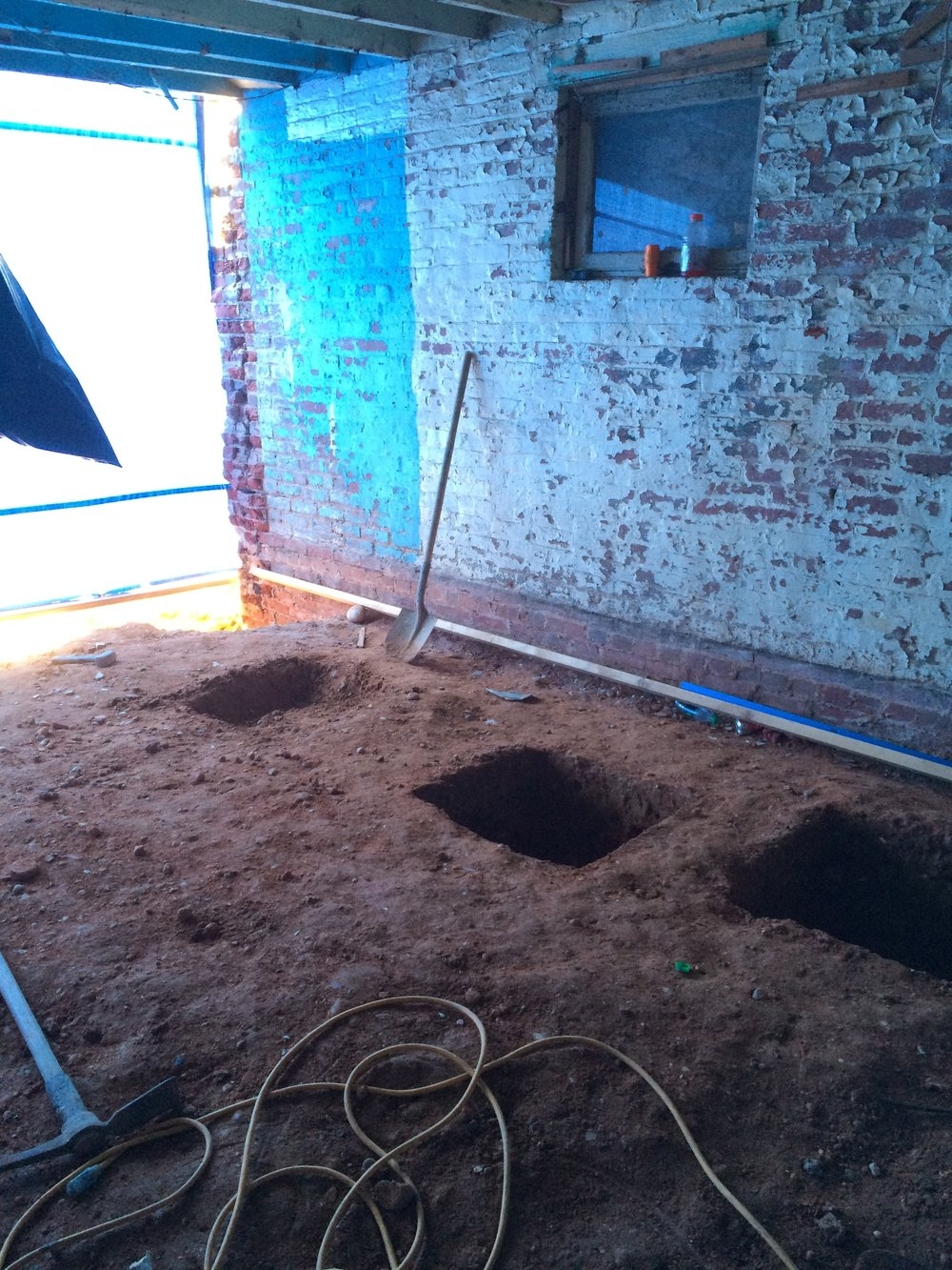 Pits dug for new footings that will support the new stairway on the interior of the house.