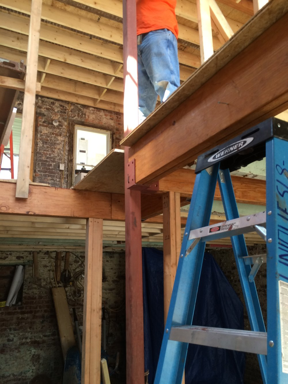 A view below the 1st floor showing the new LVL beams, Advantech sheathing, and the new steel posts place