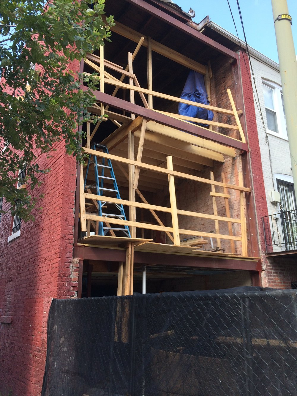 View from rear alley with scaffolding removed showing steel frame in place and new floor framing in progress
