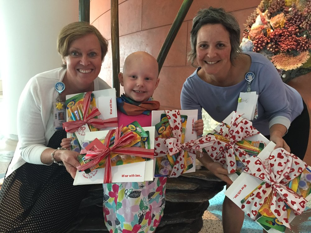 "Rosie donating ""Scarf Making Kits"" to Susan Ruohonen (Director of Children's Services) and Willow Messier (Art Therapist).  They are responsible for spreading the Coming Up Rosies love at Lurie Children's Hospital!"
