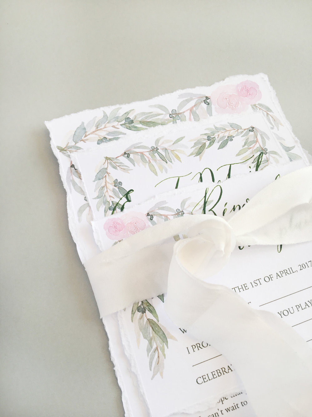 Using soft silk ribbon for tying an invitation suite together