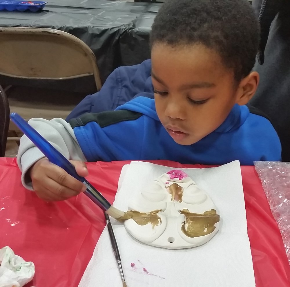 JB painting an African mask during the 2015 Indianapolis Kwanzaa Celebration held at Crispus Attucks High School.