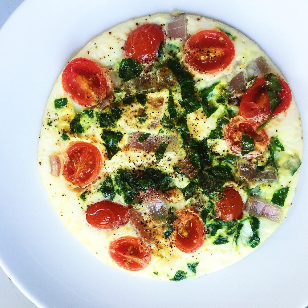 Fried egg white topped with sliced cherry tomatoes, diced red onion, chopped spinach, black pepper and sea salt