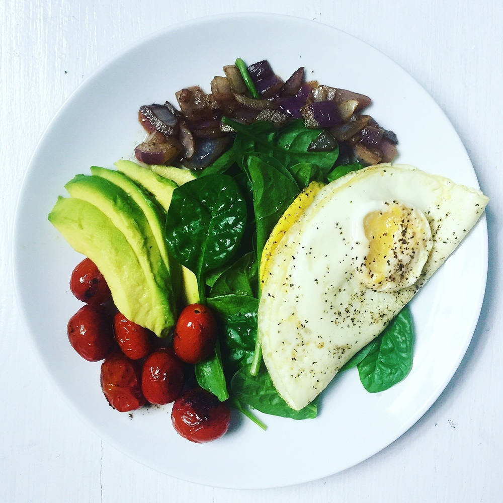 Fried runny egg over spinach leaves with avocado wedges, sautéed cherry tomatoes and red onion on the side, seasoned with black pepper
