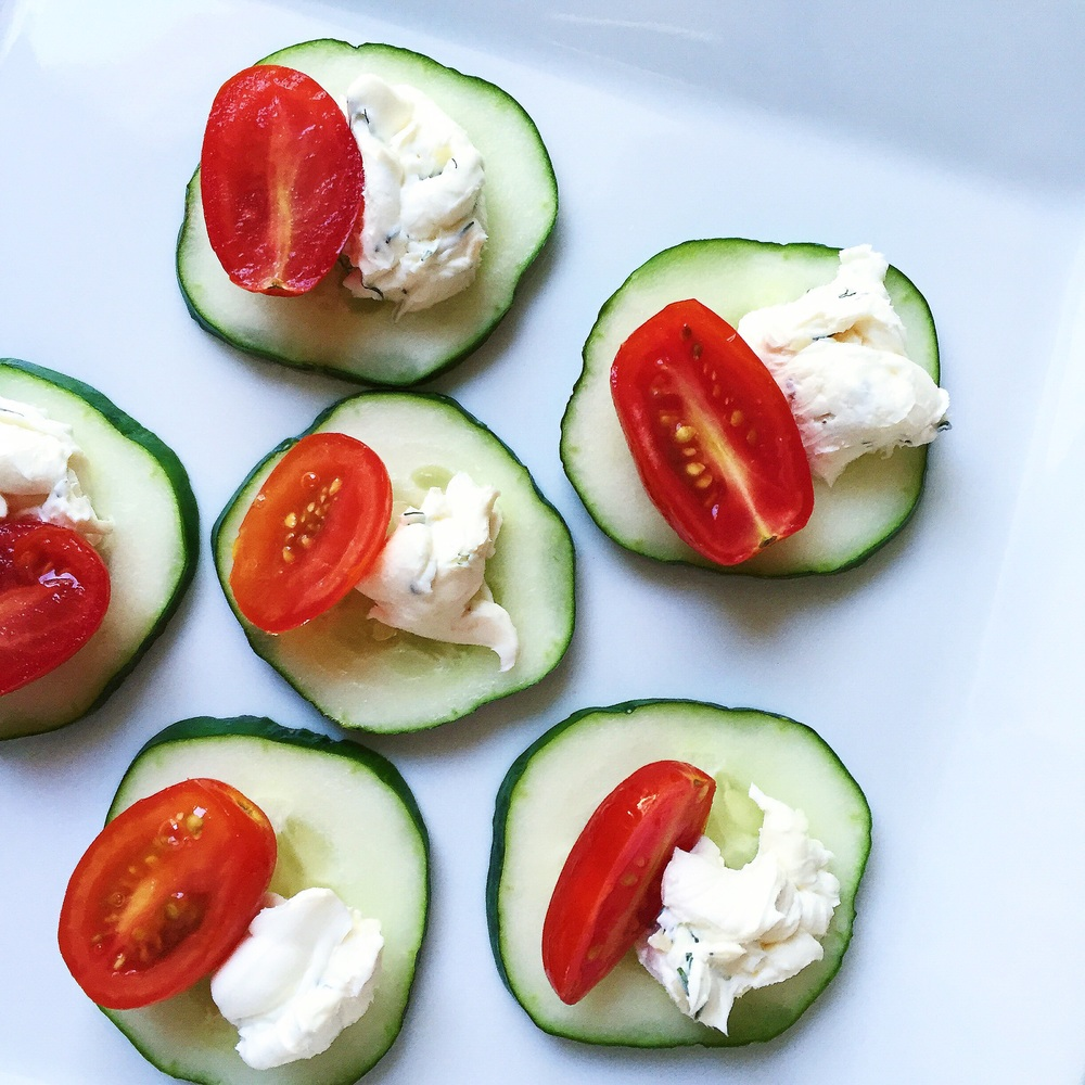 Sliced cucumber garnished with cherry tomato and garlic-dill cream cheese
