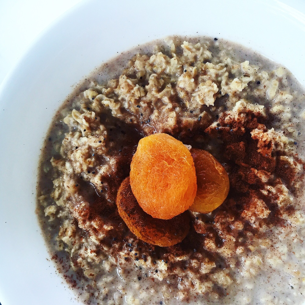 Oatmeal cooked in milk and brown sugar, garnished with dried apricots, cinnamon and poppy seeds