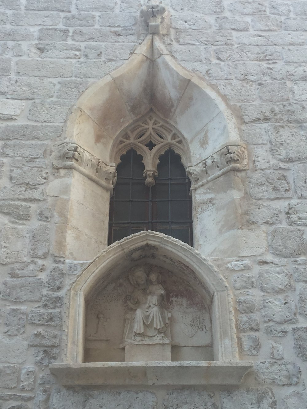 A detail on a patrician house in Šibenik. Notice the latticed window carving and cornichon. The white marble stone of Dalmatia was used in the construction of all Gothic, Romanesque, Renaissance and Baroque building.