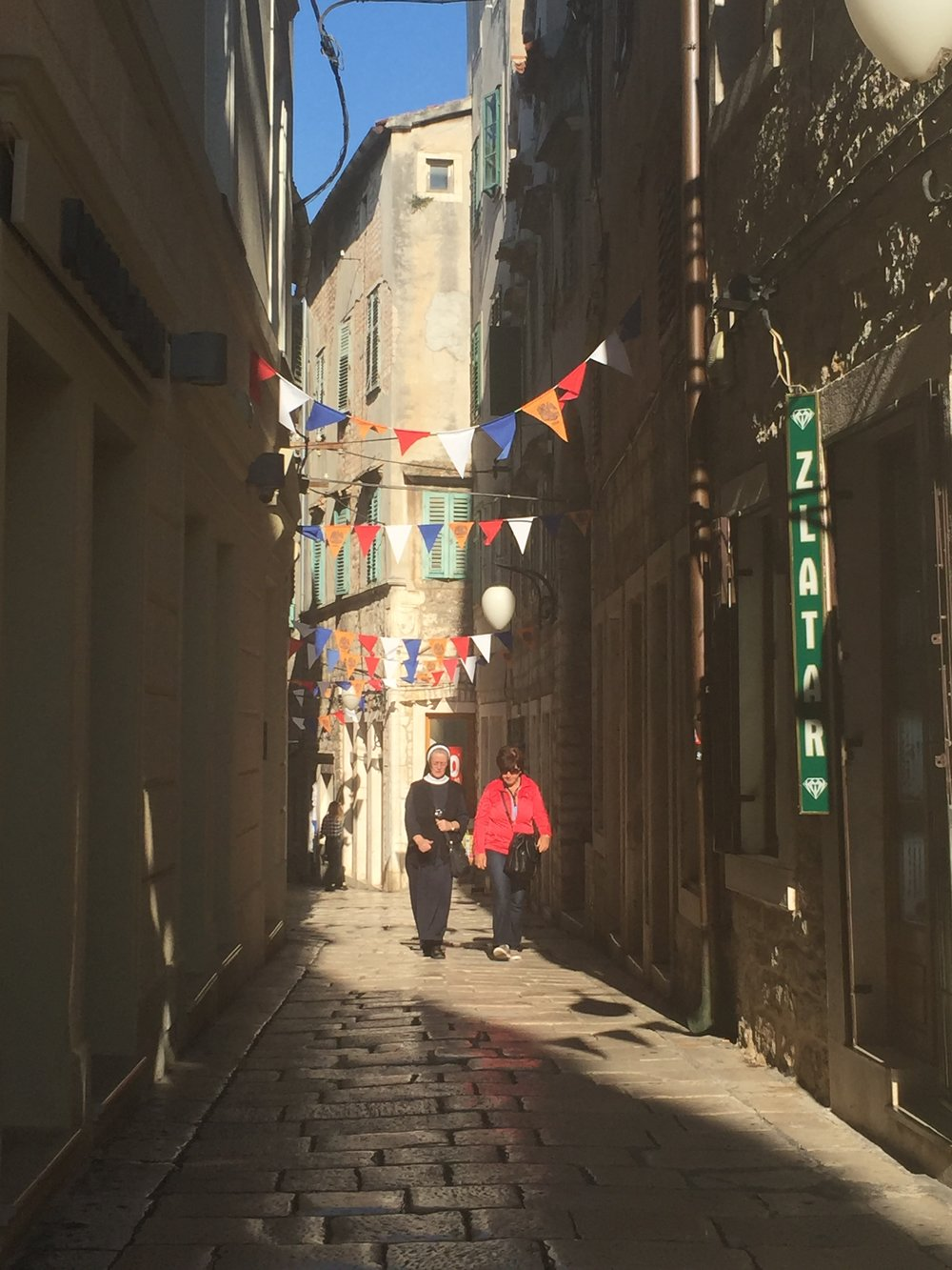 Quiet walk in a sunlit side street of old Šibenik. I actually took this photo and am quite proud of it. Evidence of the old and the new in Dalmatia blend in harmoniously.