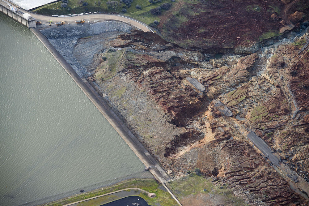 An aerial photo of the emergency spillway at Lake Oroville shows signs of major damage. The water level dropped Monday, reducing the risk of a catastrophic spillway collapse. (Randy Pench / The Sacramento Bee)