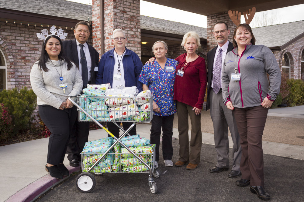 BCC Delivery: NIHD employees also gathered 39 gifts for the residents of Bishop Care Center. Shown with the cart of gifts, which the NIHD team pushed to neighboring BCC's front door, are from left to right, NIHD's Michelle Garcia, BCC Administrator Jay Caramba, BCC Director of Nursing Sue Uchendu, BCC Activities Assistant Cora Heeg, BCC Activities Director Ida Enger, NIHD CEO Dr. Kevin S. Flanigan, and NIHD's Kristen Bernasconi. Photo by Barbara Laughon/Northern Inyo Healthcare District