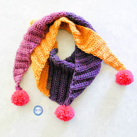 "My ""mod scarf"" patterns are some of my favorites, so I decided to make a mini version for my daughter!  This simple and modern scarf is adorned with pom poms and is perfect for children.  Keep reading for the free crochet pattern."