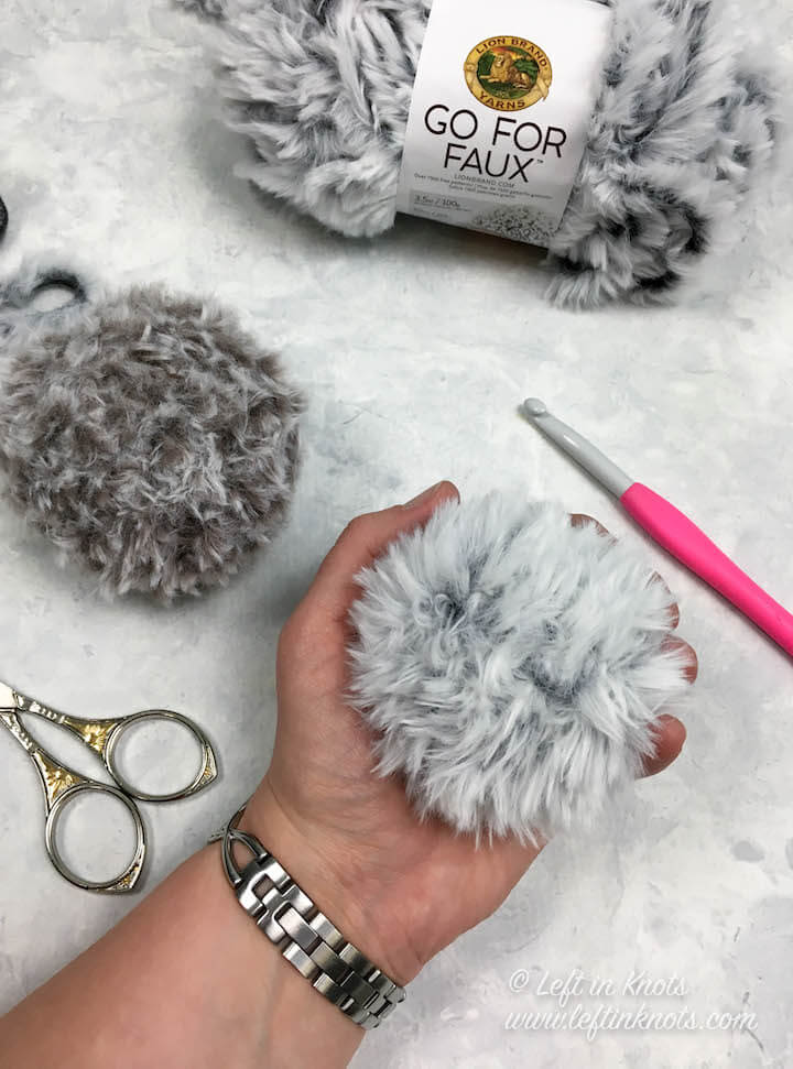 """Faux fur pom poms are so hot right now, and they are hard to find for an affordable price. So Lion Brand Yarn has saved the day with their new  """"Go For Faux""""  yarn. It is so soft and fluffy, and it makes excellent faux fur pom poms perfect for adding the finishing touch to all your crocheted or knitted hats! Keep reading for the free crochet pattern."""