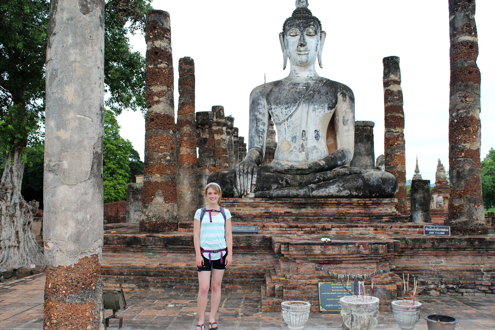 Standing in front of a Buddha statue in Sukhothai Historical Park, Thailand.
