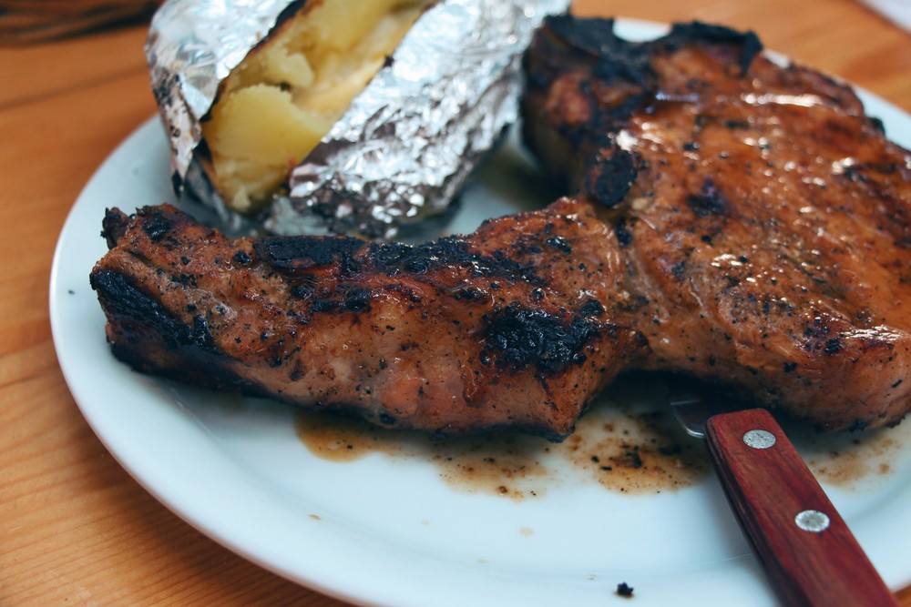 BBQ grilled pork steak served with a hot potato right from the grill