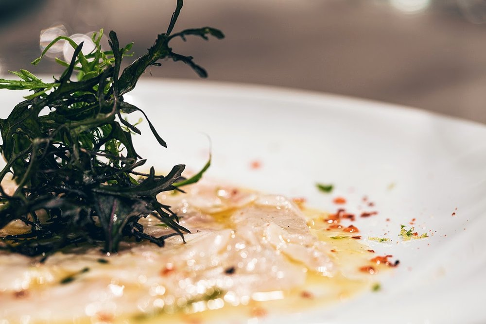 Seabass carpaccio sprinkled with citrus zest, chilli drops and a dash of wild rocket