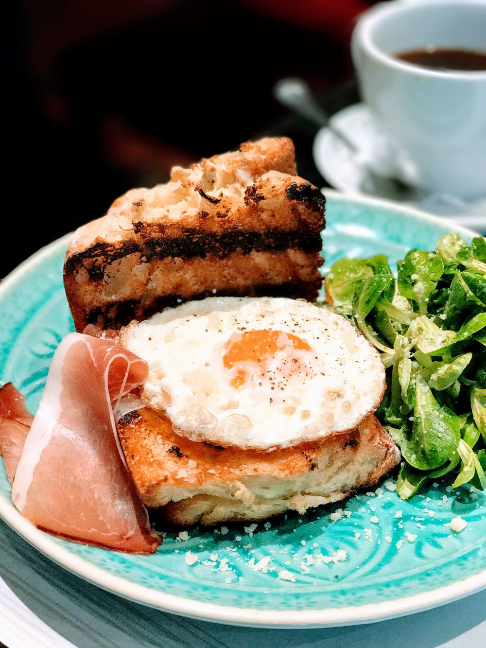 Croque Madame served with a few slices of prociutto and green salad