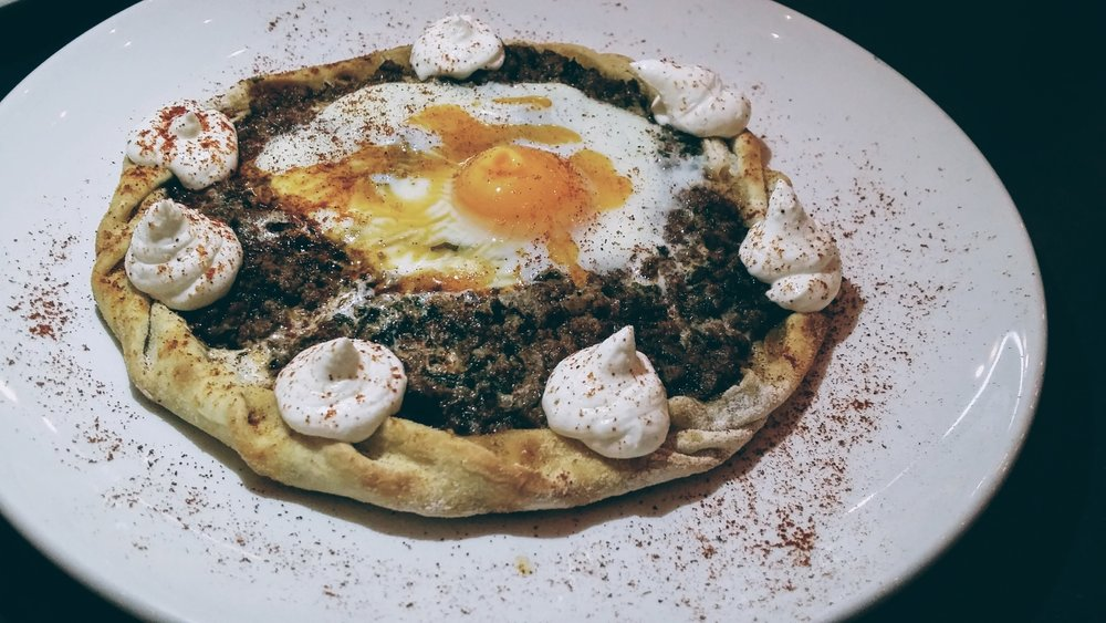 Baked minced meat pie, garnished with a medium cooked egg