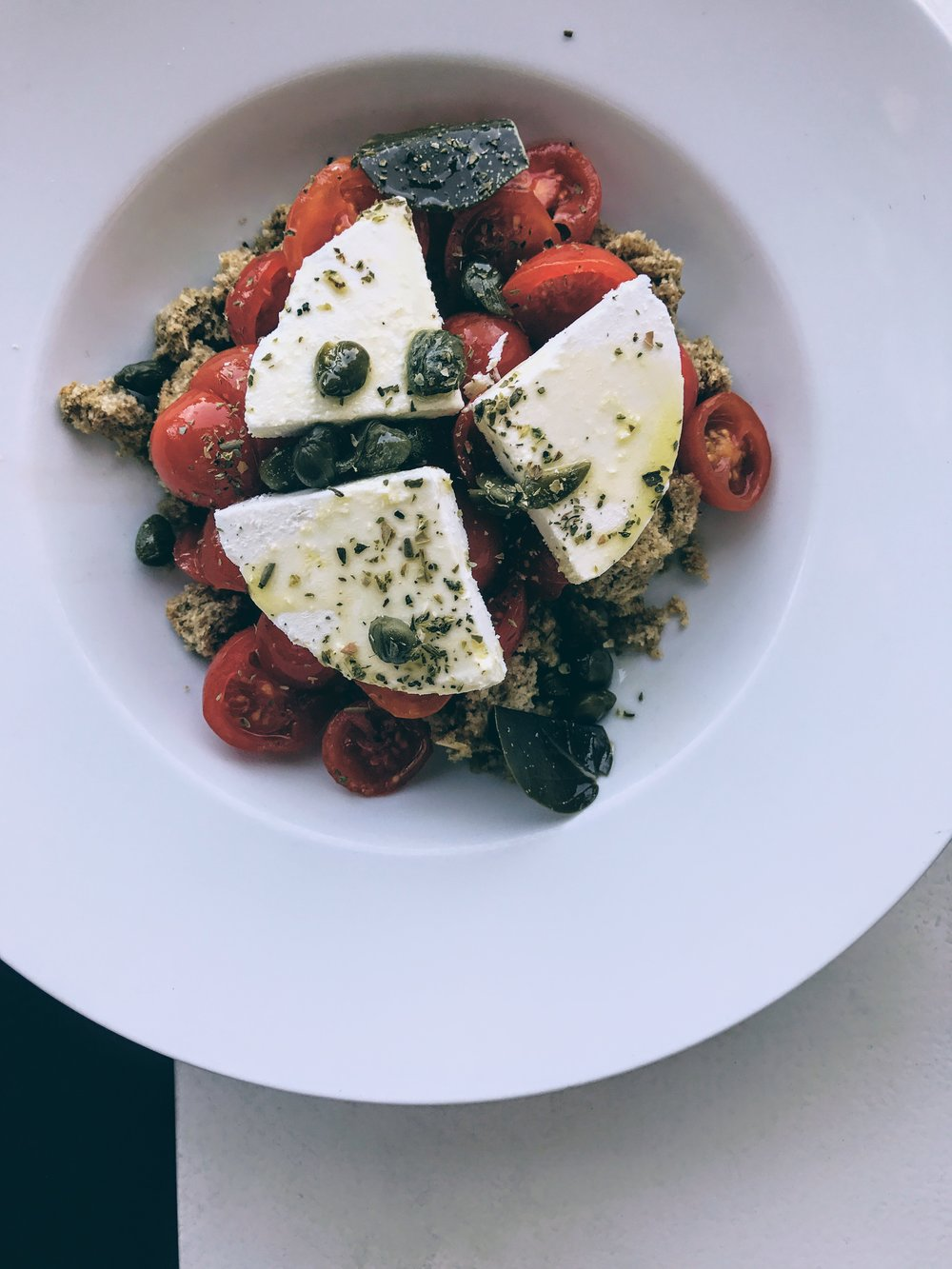 Pomodorini tomato salad with Cretan rusk, caper leaves and Mykonos xinomizithra cheese