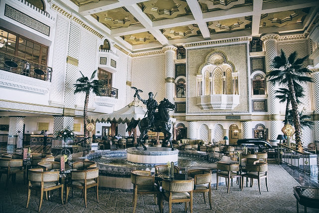 The ornate lobby of the Hyatt, and the outdoor pool area of the Al Bustan Palace / Source: Wikimedia Commons
