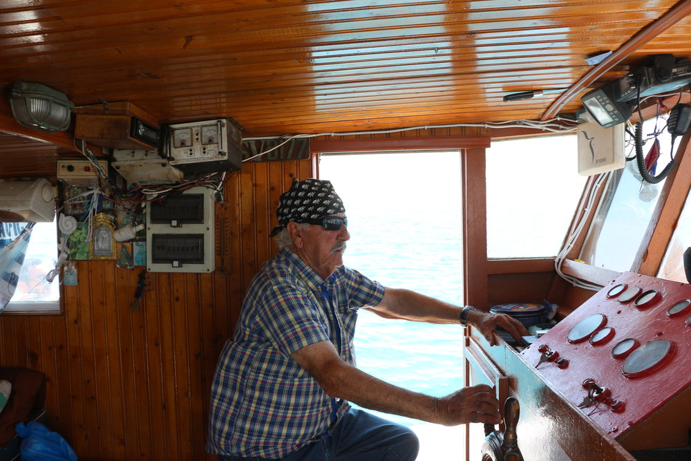The most cult guy on the island, Mr Costas manning his boat to Kato Koufonisi