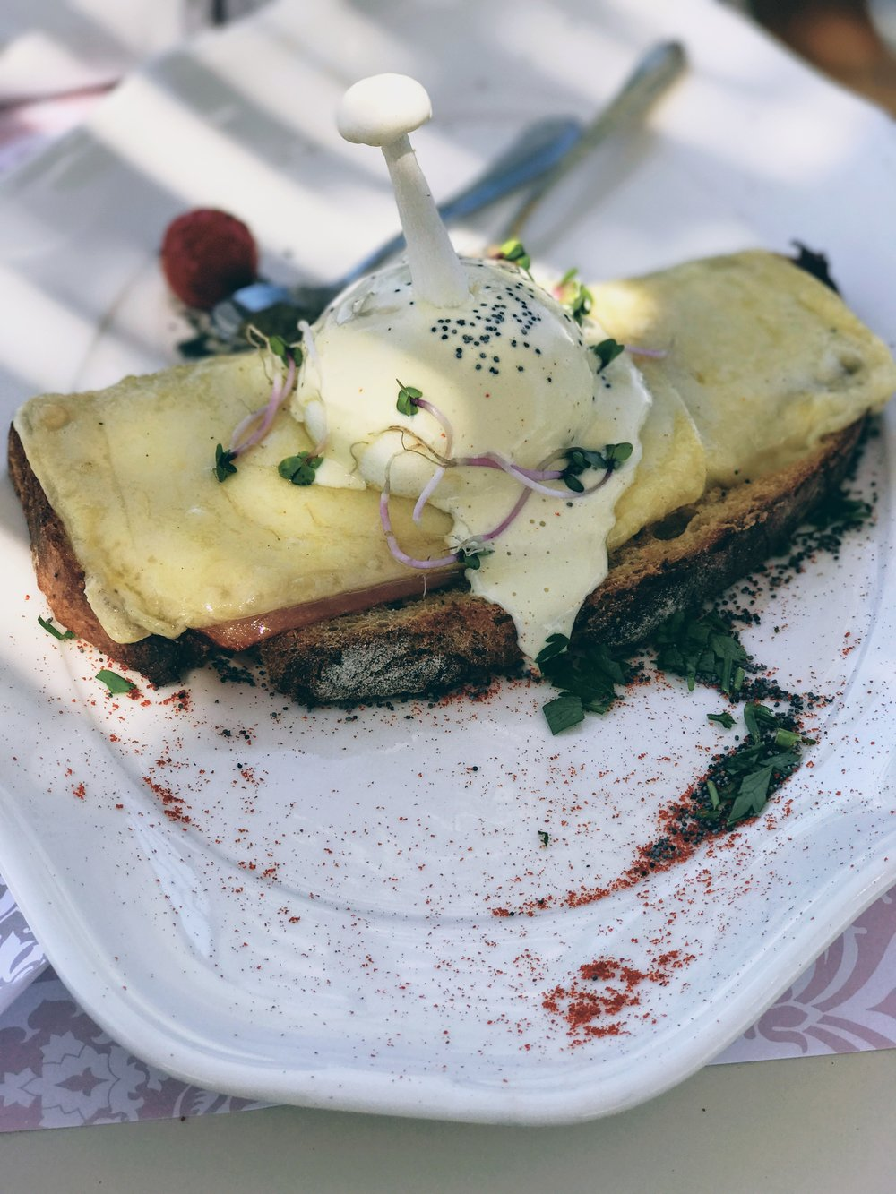 Poached eggs served on farmer's brown bread and a bed of Naxos gruyere cheese and ham