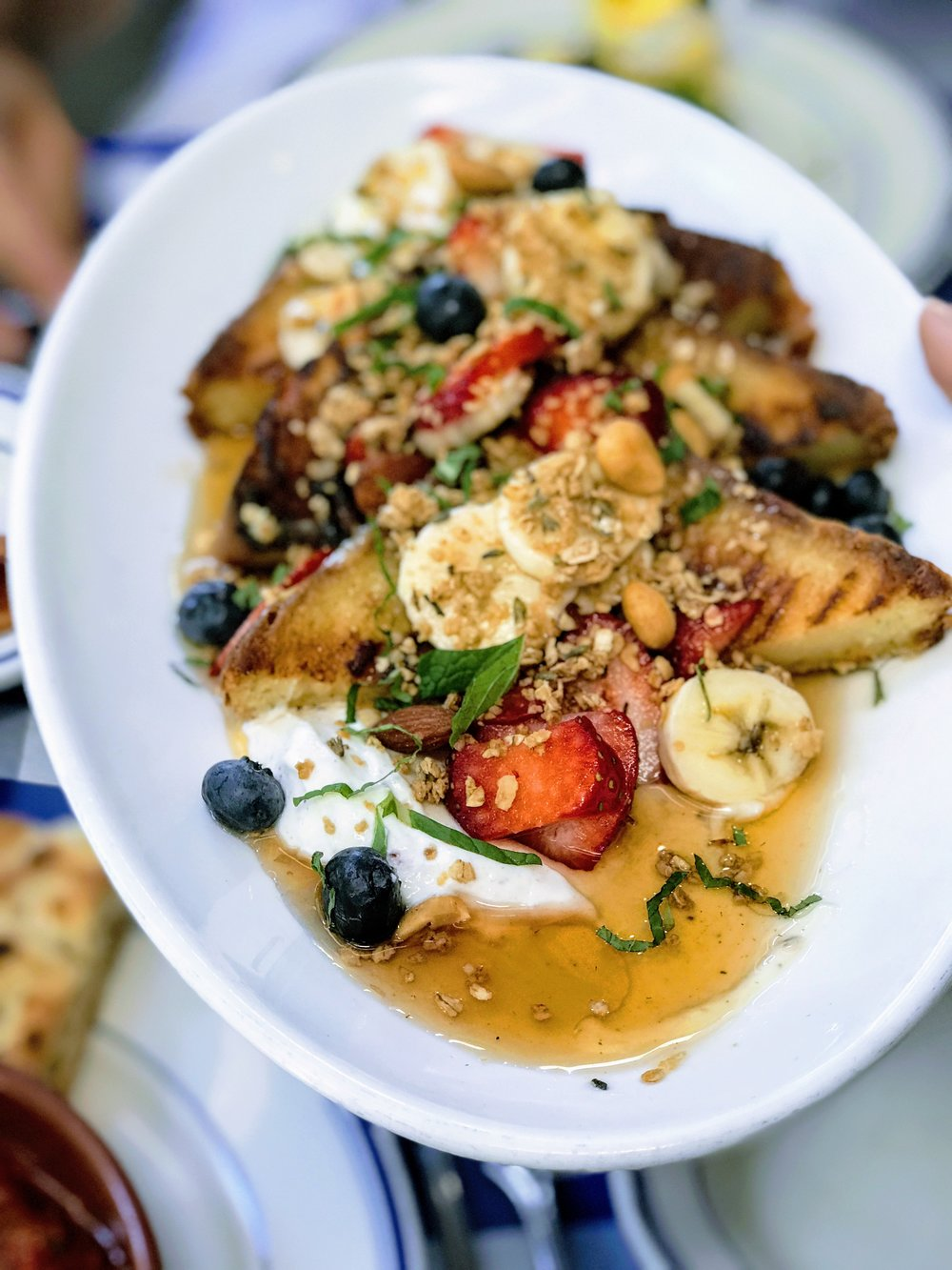French toast covered in honey, fruit, mint and pecan nuts