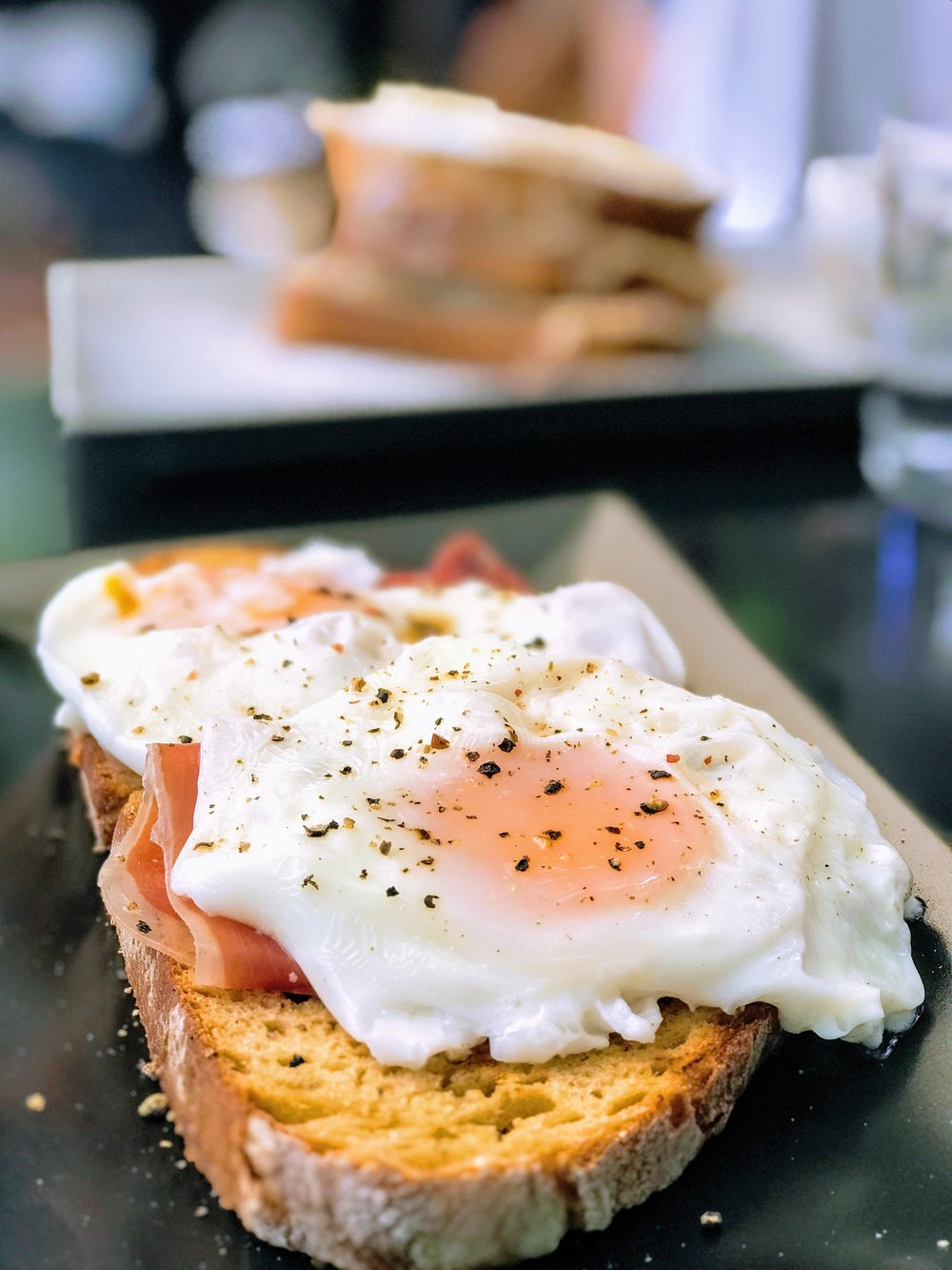 Poached eggs with prosciutto on farm bread