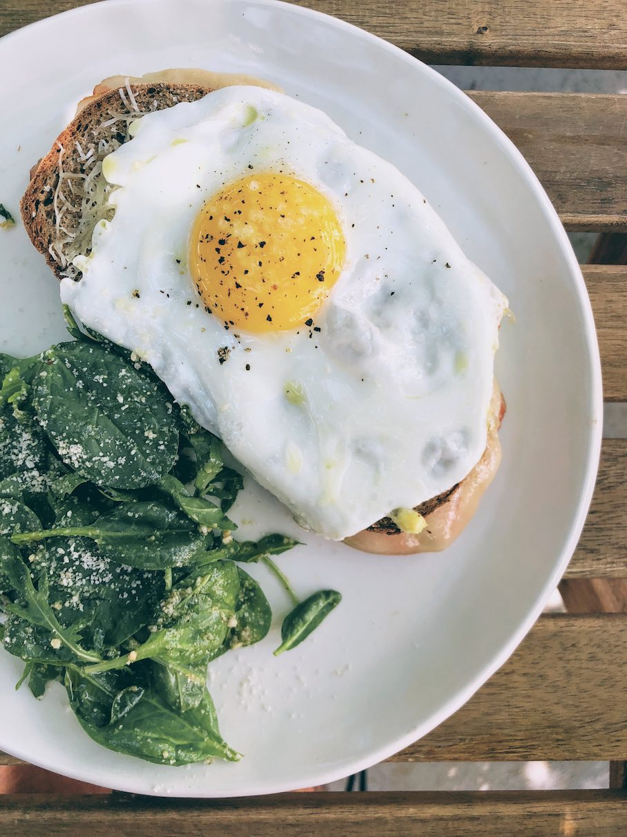 Egg on toast with shredded Naxos gryere cheese and side spinach salad