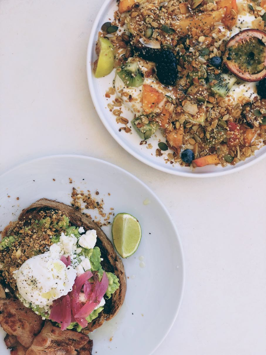 Hearty yoghurt and fruits dish and avo toast with poached egg, pickled onions and dukkah with a side of bacon