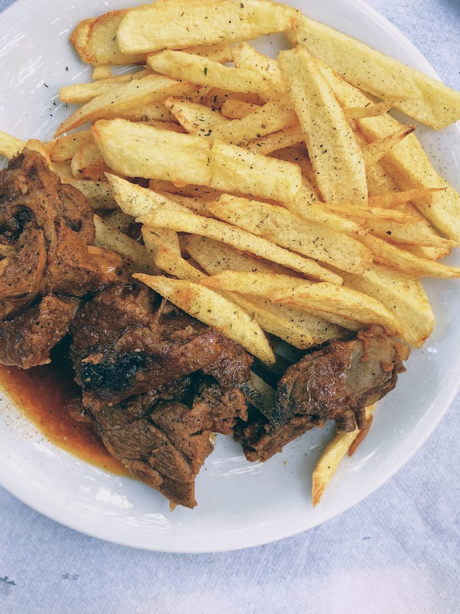 Goat stew in tomato sauce and thick-cut french fries