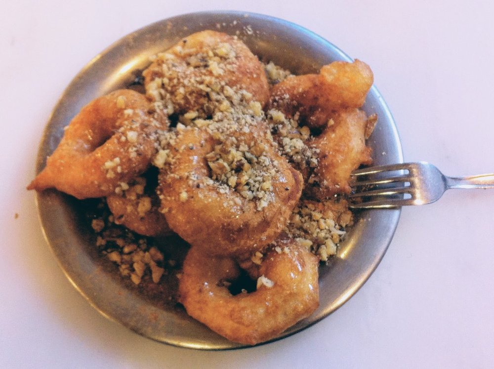 Honey-glazed doughnuts sprinkled with crushed walnuts at Krinos