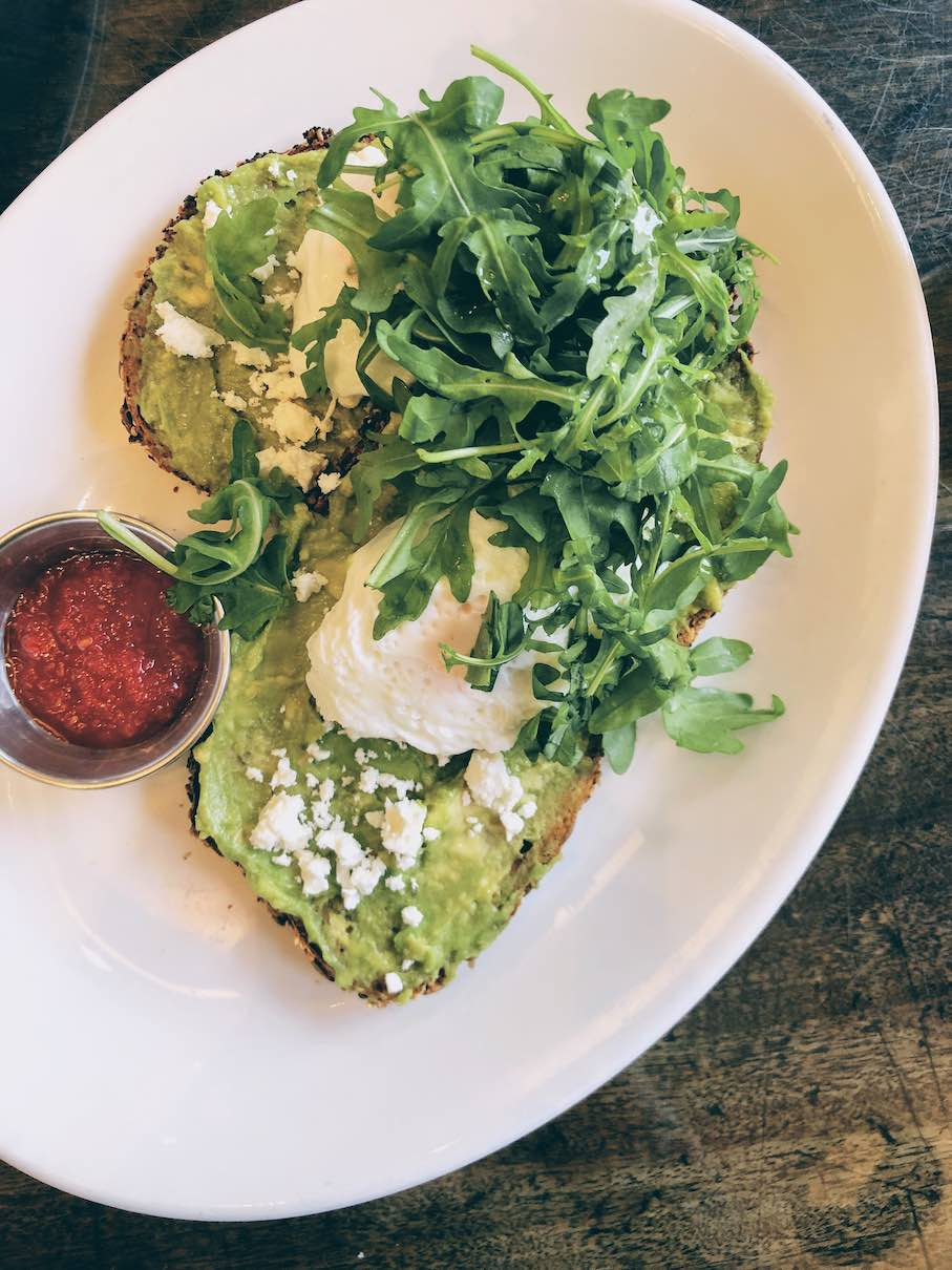 Avo toast with poached eggs and feta cheese crumbs