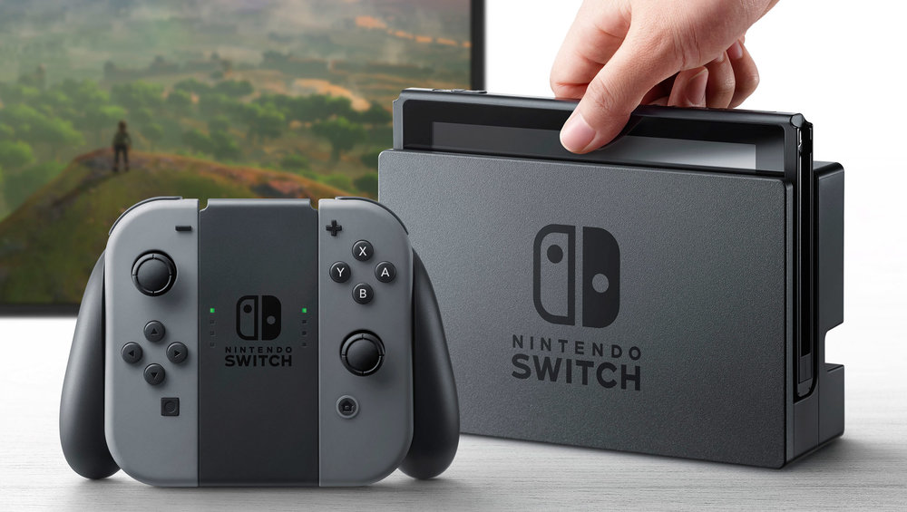 Source: Forbes | The Nintendo Switch docked in its holder with the controller pieces attached to the grip attachment accessory.