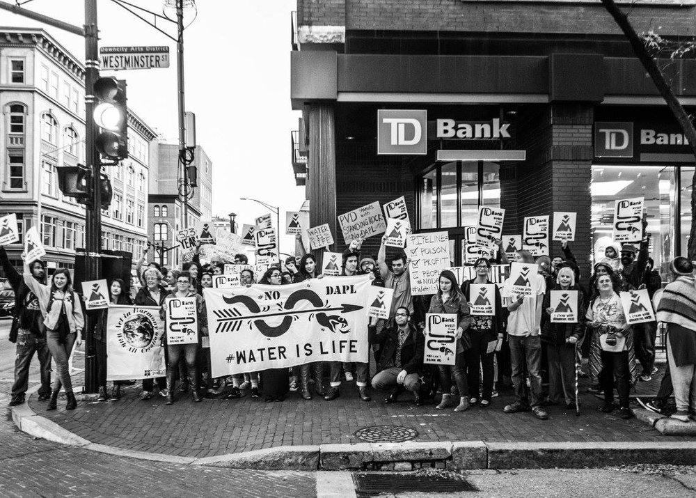 "image description: group of over 25 people gathering in front of a TD Bank branch in Providence, RI holding signs that read: ""Water is Life,"" ""No DAPL,"" ""TD Bank Finances Police Brutality,"" and ""TD Bank Divest from DAPL"""