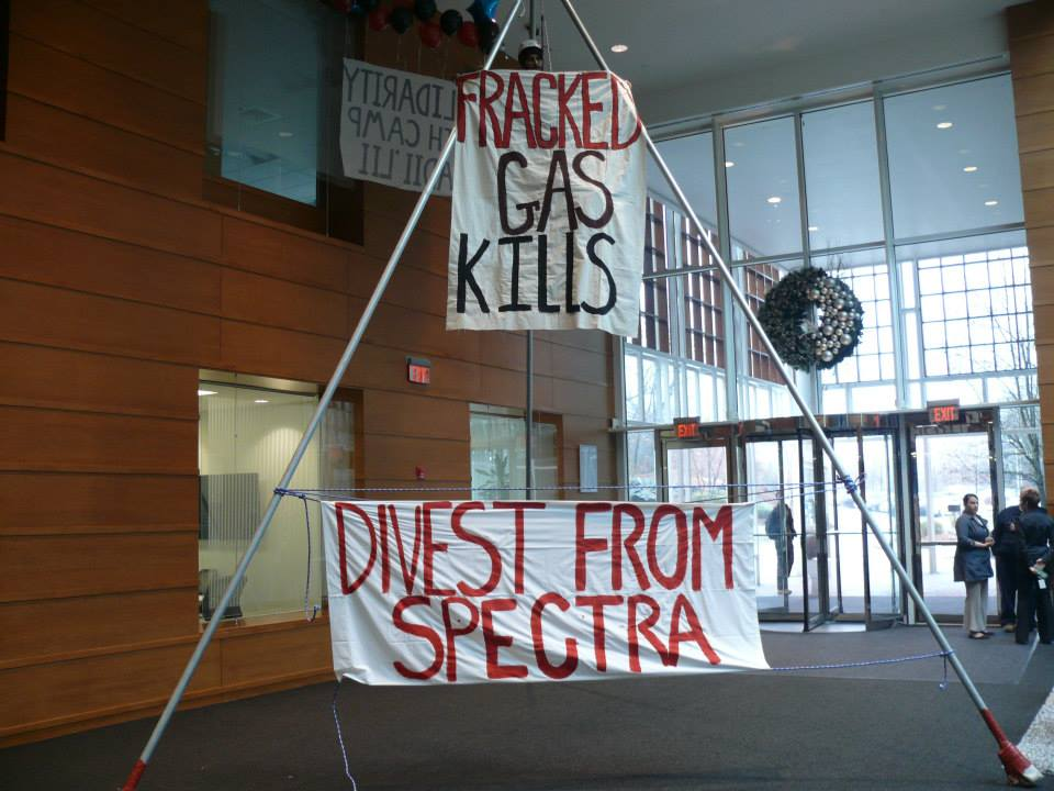 "image description: 30 ft. three poled structure (tripod) with a climber at the top holding a sign that reads: ""Fracked Gas Kills"""