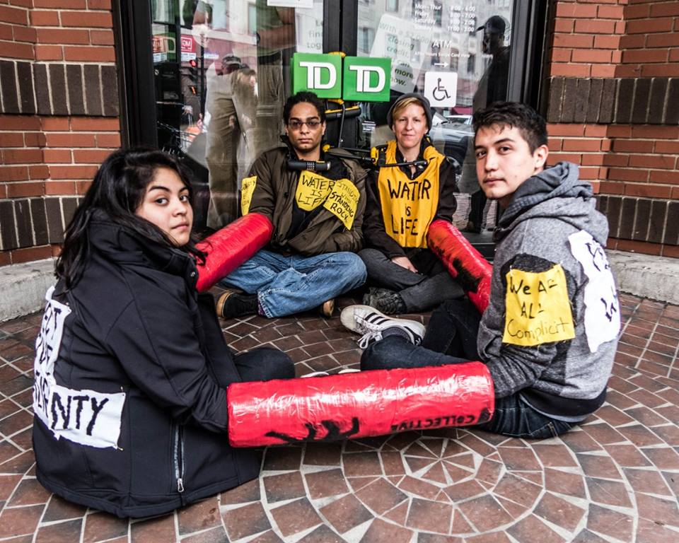 "image description: 4 people sitting on the ground locked to themselves and the front doors of a TD Bank branch in Providence, RI; wearing patches with the messaging, ""Water is life,"" ""We are all complicit"""