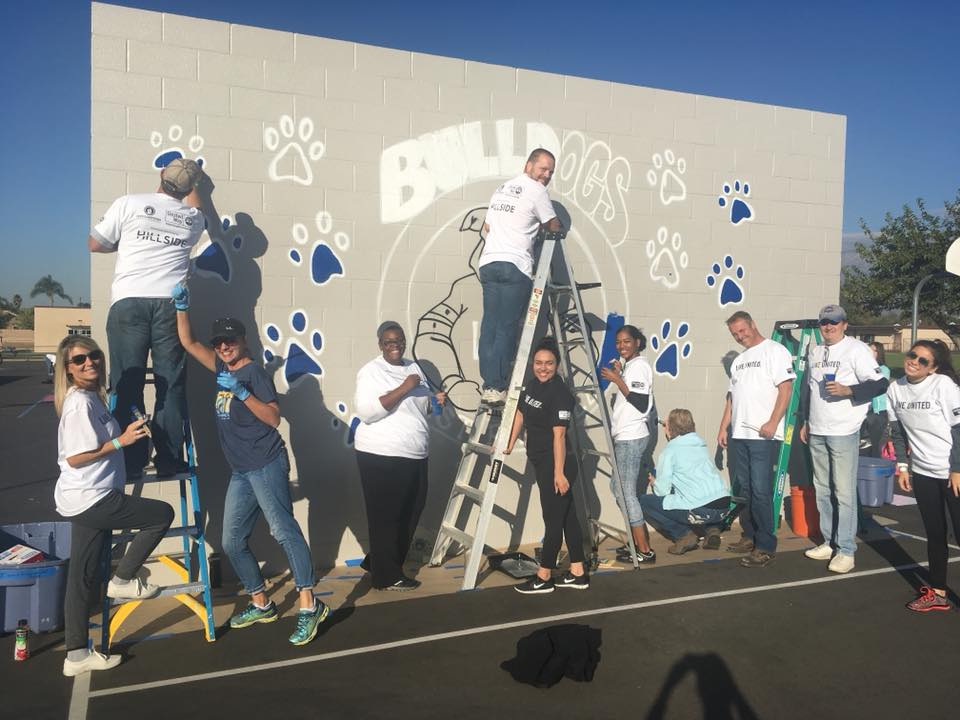 Volunteers work to complete the mural on the West Randall Elementary Playground, led by IEUW Americorps, Carly Corona. photo courtesy of IEUW