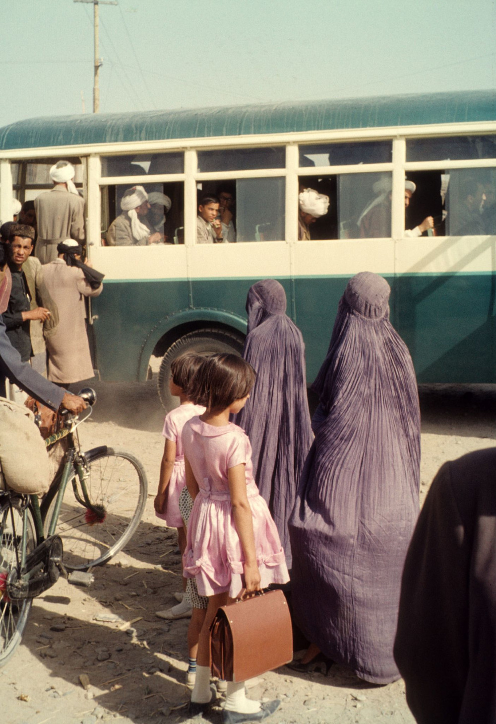 oldafghanistan: Title: Setting Off  Description: Two Afghan Women, and their daughters, wait in a queue to board a bus in the Capital.  Location: Kabul, Eastern Afghanistan.  Circa: 1965