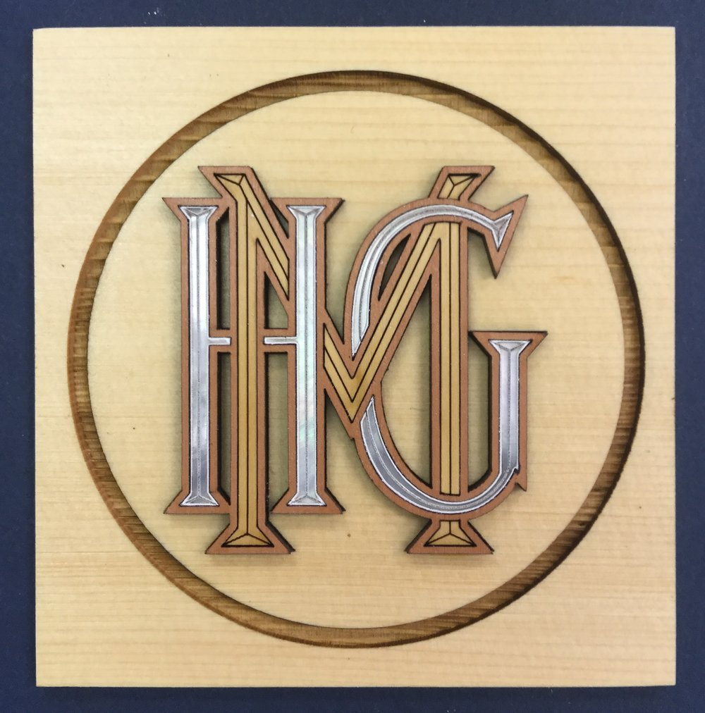 Williamstown Art Conservation Center   Replacement monogram for a pair of  19th century piano stool  designed by Sir Lawrence Alma-Tadema. Laser-cut pear and boxwood monogram inlayed into laser-engraved juniper,