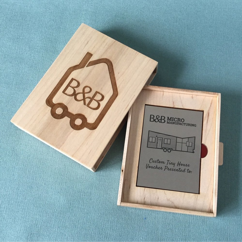 This voucher was commissioned by a client, who gifted a tiny house to her husband for his birthday. Pike created the maple box with sliding drawer, engraved the company logo on the box lid, and laser-marked the stainless steel voucher inside.