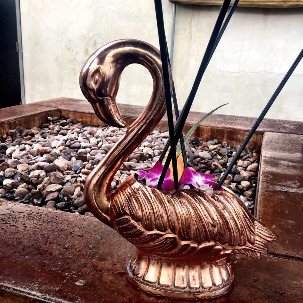 rum cocktail out of a rose gold flamingo at miss b's coconut club san diego
