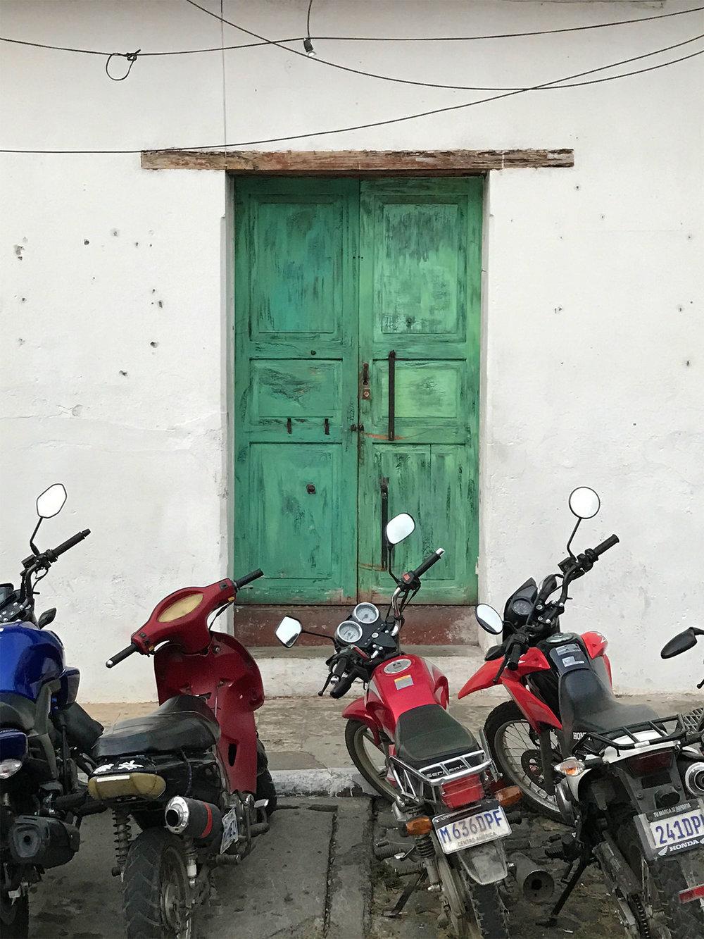 blue door and motor bikes in Antigua, Guatemala
