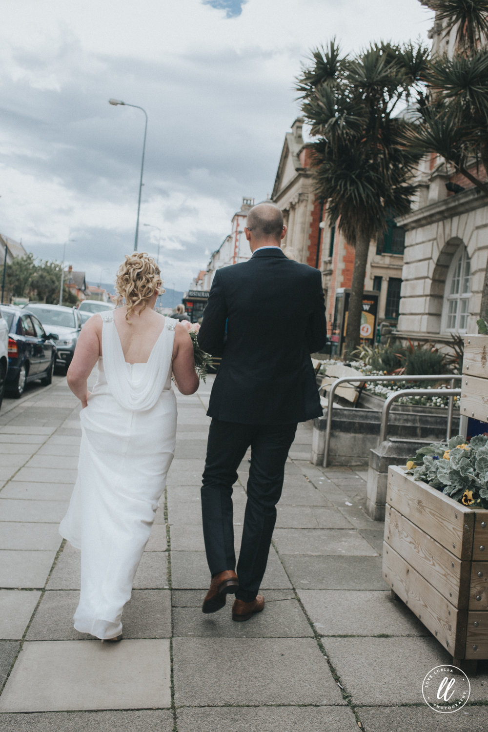 The bride, groom and their son walk through llandudno town