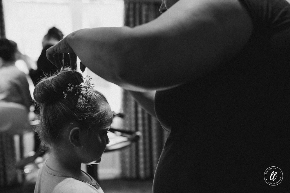 Black and White image of a flower girl getting ready