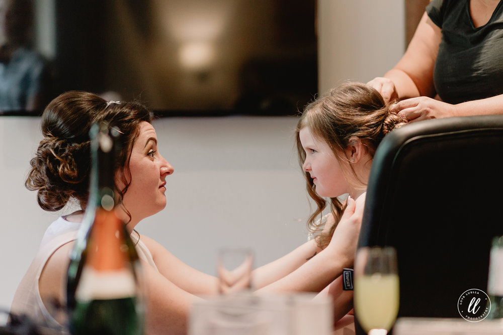 The bride giving her daughter/flower girl some cheering on through the boring task of getting her hair done up.
