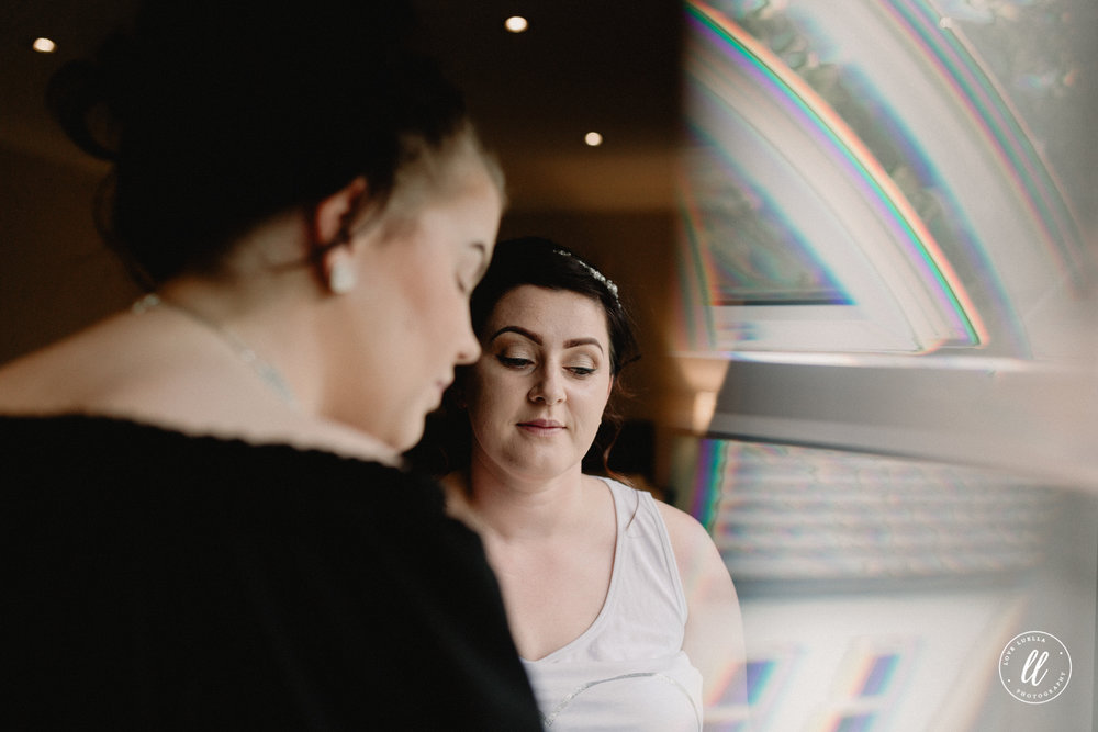 A candid image of the bride using a prism effect at the window