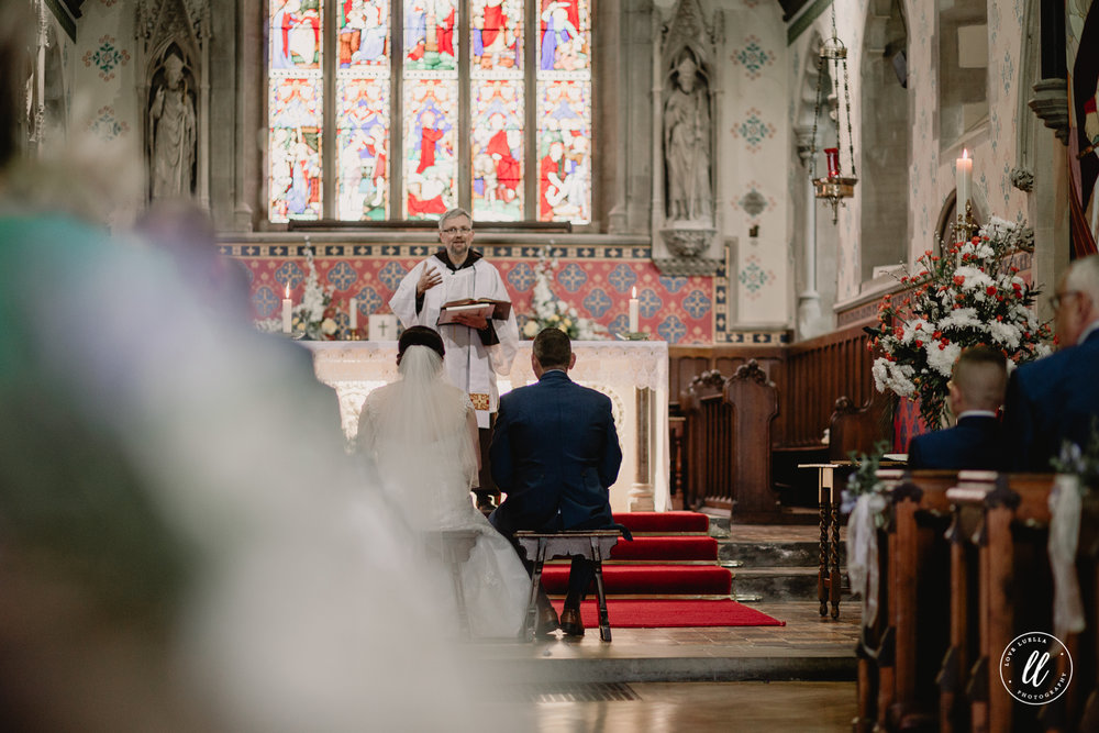 The bride and groom take a seat at the top of the friary aisle listening to their family read