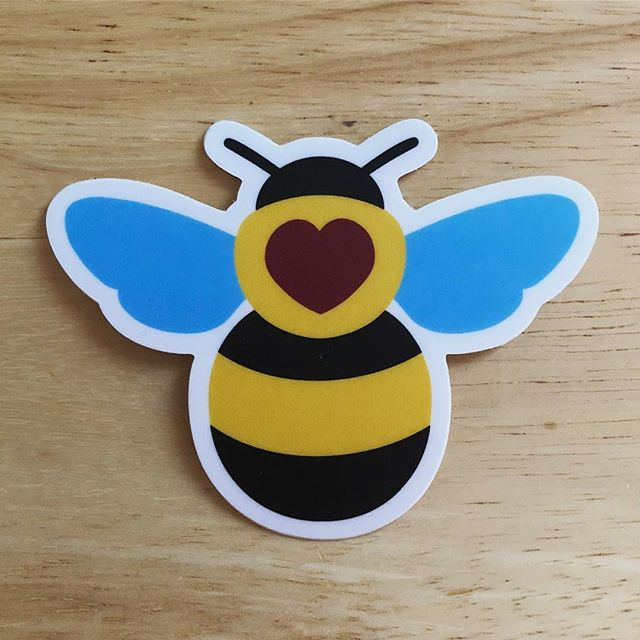 Just in time for #SmallBusinessSaturday, I've got a new sticker in the shop! Adorable, chubby heart bees, check em out at the link in my bio.  #sciart #bees #bumblebee #savethebees #scicomm #nature #botany #biology #science @stickermule #sticker #vinylsticker - - [Image: a sticker of a black and yellow bumblebee with a red heart on its back, sitting on a wooden surface.]
