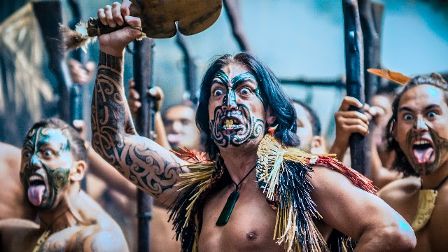 """In 1820, the great Northern War Chief Hongi Hika departed New Zealand for England. On his return, he brought with him the word of God and hundreds of muskets. Things would never be the same again …""     … so begins the video for Alien Weaponry's new single, 'Kai Tangata'.  The title literally translates to 'Eat People'; and refers to the ancient Māori tradition of eating the flesh of their enemies after battle in order to insult them. It is also an ancient term for a war party.  In their epic 7-minute song, the thrash metal trio recreates the memory of the early 19th Century musket wars, where Ngapuhi (Northern) tribes, newly armed with muskets, attacked and decimated the de Jong brothers' Te Arawa (Central North Island) ancestors, who at that time were still using traditional weaponry.  Watch 'Kai Tangata' right   HERE  !    The driving riff that carries the song echoes the pounding footsteps of the war party, while the chorus traces the parts of the full body moko (tattoo) traditionally worn by Māori warriors. The images are of brutal hand-to-hand combat and the taking of slaves, with flashes of white teeth reminding us of the eventual fate of those unfortunate captives.    ""Some people might find it a bit grisly,"" says singer and lead guitarist Lewis de Jong. ""But it's stuff that actually happened and nobody ever talks about it. We're not saying it's right or wrong, it's just a part of our history.""   The song refers to 'nga tohu a Tūmatauenga' (the symbols of Tūmatauenga – the Māori god of war), and it is from this deity that the band's debut album,   ""Tū""  , takes its name.   ""Quite a few of the songs on the album are about battles or conflict,"" says drummer Henry de Jong, who was largely responsible for the lyrics of Kai Tangata. ""So we thought it was appropriate to name the album after Tūmatauenga. Tū also means to stand strong and proud, to stand for something; which we think is important as a band and as people.""   The video has special significance for the band due to the locations and people involved. Parts of the clip were filmed at the Waipu Caves, not far from where the band members live. The rest was filmed in the de Jong brothers' Te Arawa tribal territory; and many of the people featured – including the kapa haka group Te Matarae i Orehu – are members of their Ngati Pikiao whanau (family) and their wider Te Arawa iwi (tribe)."