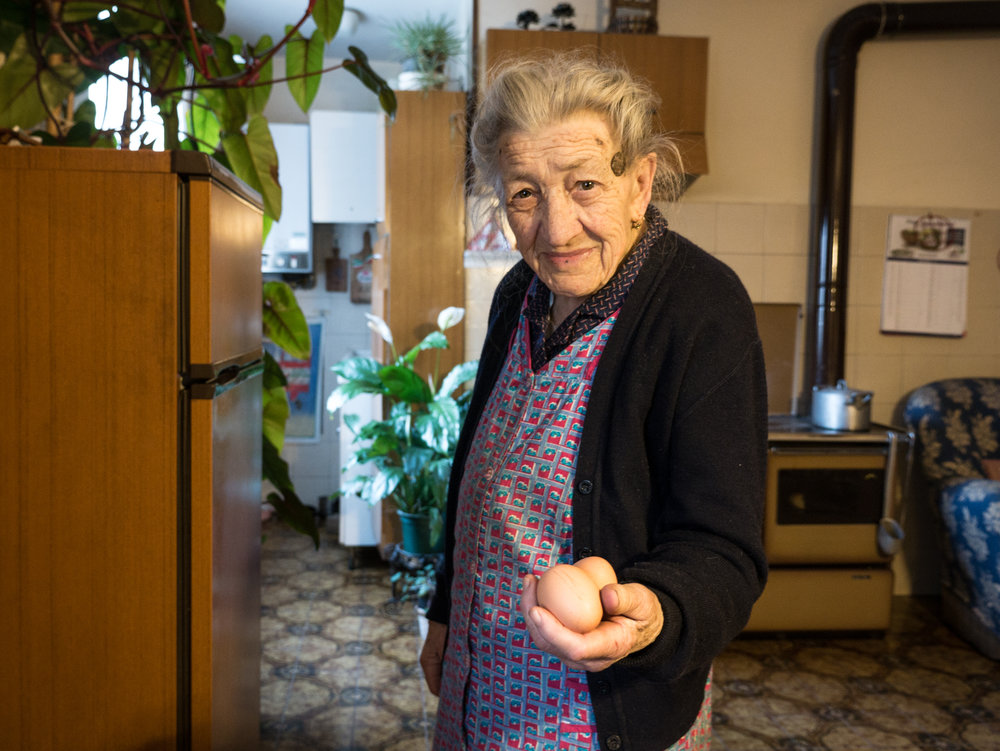 """Grandma shows me two eggs of one of her two hens. """"The other one stopped producing, but it keeps company anyway""""."""